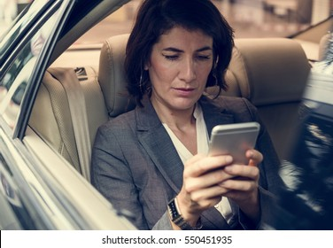 Businesswoman Using Smart Phone Car Inside