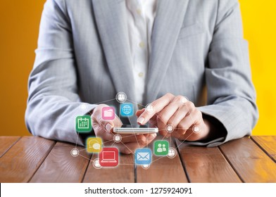 Businesswoman using smart phone. Communication concept, application icons flying around