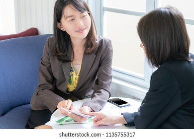 businesswoman using smart phone and meeting with colleagues to discuss financial results