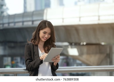 Businesswoman using smart phone or tabletat Outside Office, woman look photo album travel. Communication technology Concept.