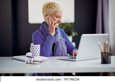 Businesswoman using smart phone while sitting in modern office. On desk laptop, mug, pencils, eyeglasses and planner