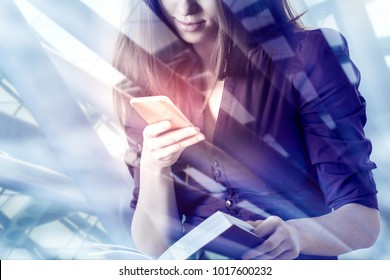 Businesswoman using smartphone with digital business interface and holding book on abstract city background. Online education, technology and media concept. Double exposure