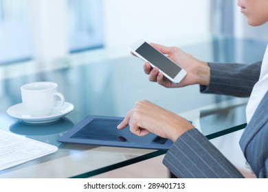 Businesswoman using smartphone and tablet in an office