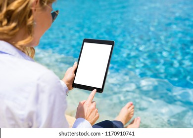 Businesswoman using tablet computer by the pool