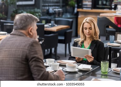 businesswoman using tablet during business meeting with colleague in cafe