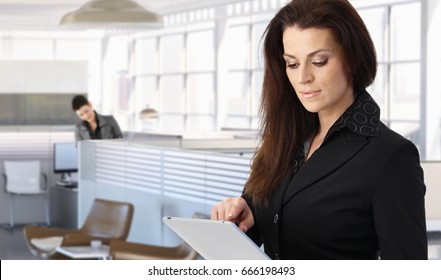Businesswoman using tablet for work in modern office.