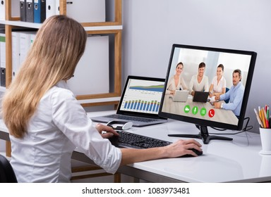 Businesswoman Video Conferencing With Happy Colleagues On Computer In Office
