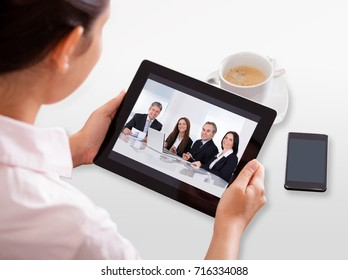 Businesswoman Video Conferencing On Digital Tablet With Cup Of Tea On Desk