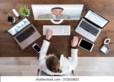 Businesswoman Videoconferencing With Senior Colleague On Desktop Computer