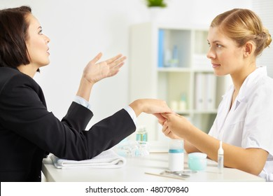 Businesswoman visiting manicurist and talking to her