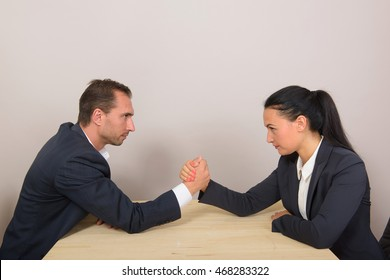 Businesswoman vs businessman - arm wrestling on working table