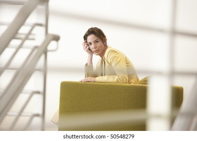 Businesswoman waiting on sofa in office, portrait