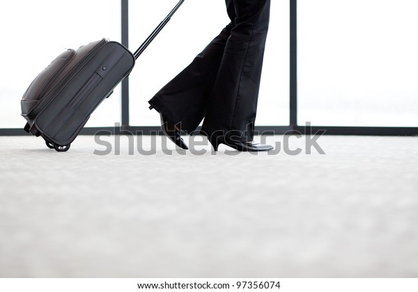 businesswoman walking in airport with her luggage