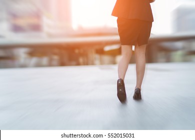 Businesswoman walking away low angle cross section in city.