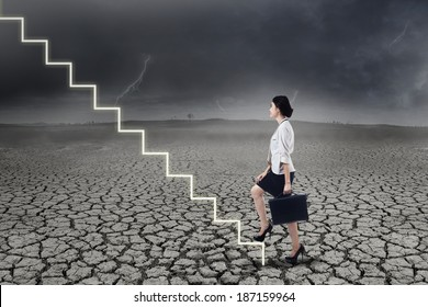 Businesswoman walking up on stairs in stormy weather