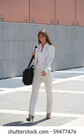 businesswoman walking outdoors in a sunny day