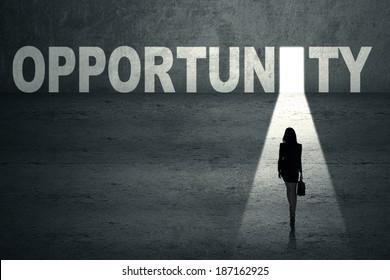 Businesswoman walking toward an opportunity door