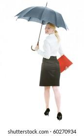 Businesswoman walking under umbrella