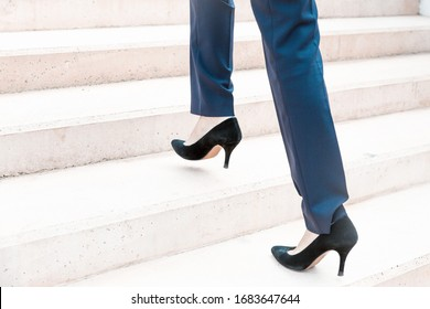 Businesswoman walking upstairs. Legs and feet of business woman wearing formal trousers and shoes. Walking to office or career concept
