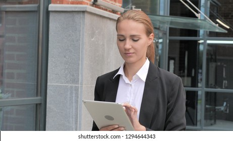 Businesswoman Walking and Using Tablet, Browsing Online