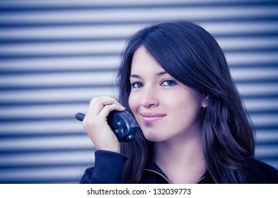 Businesswoman in warehouse using walkie-talkie