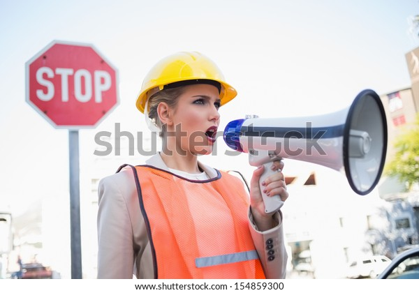 Businesswoman wearing builders clothes shouting in megaphone outdoors on urban background