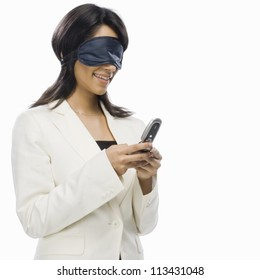Businesswoman wearing eye mask and text messaging