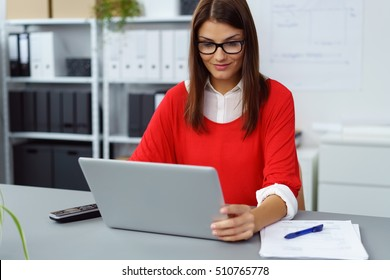 Businesswoman wearing glasses and a colorful red jersey working at a laptop computer at a table in the office reading the screen with a smile