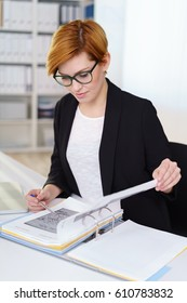 Businesswoman wearing glasses sitting consulting notes in an office binder paging through the graphs with a pen in her hand making notes