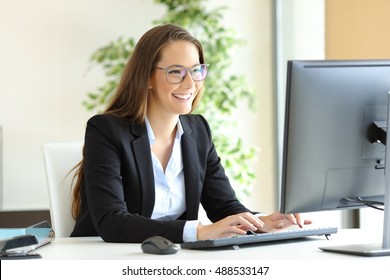 Businesswoman wearing glasses working with a desktop computer at office