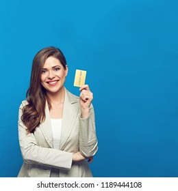Businesswoman wearing gray suit holding gold credit card. Studio isolated portrait.