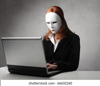 Businesswoman wearing a mask and using a laptop