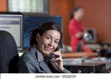 Businesswoman wearing a suit is smiling while talking on the telephone in an office environment. Horizontal shot