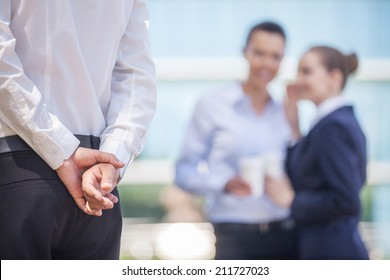 Businesswoman whispering in businesswoman's ear at office. employee whisper about colleague at break