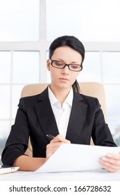 Businesswoman at work. Confident young business writing something on paper while sitting at her working place