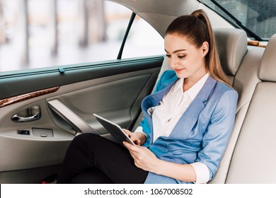 Businesswoman work with digital tablet computer and holding cup of coffee in back seat of luxury car