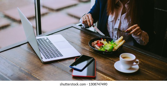 Businesswoman work in restaurant. Woman sitting with a laptop in a cafe and eating breakfast with a cup of coffee on the table.