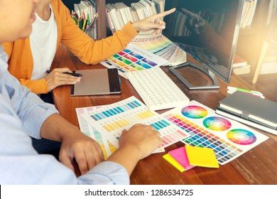 Businesswoman work and showing computer screen to coworker business man with Color swatch samples on table in creative office.   Graphic designer concept
