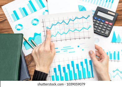Businesswoman working with business documents looking at financial charts. Business concept.