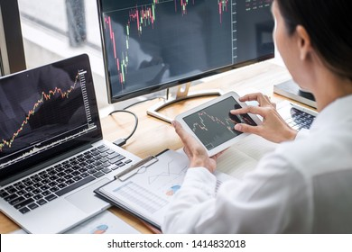 Businesswoman working with computer, laptop, thinking and analyzing graph stock market trading with stock chart data planning, financial and investment concept.