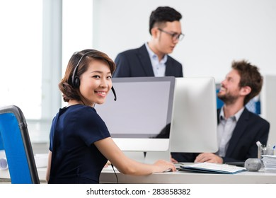 Businesswoman working at computer and smiling at camera