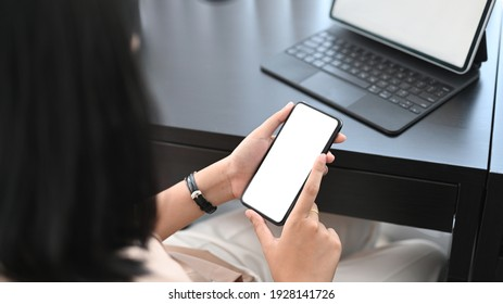 Businesswoman working with computer tablet and using smart phone searching information online at office desk.