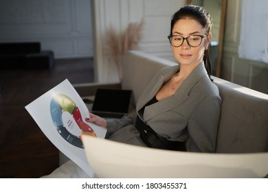 businesswoman working documents. favorite career, life's work. grey stylish suit. glasses smile at the face.