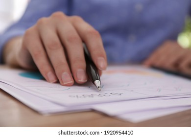 Businesswoman working with documents at table in office, closeup. Investment analysis