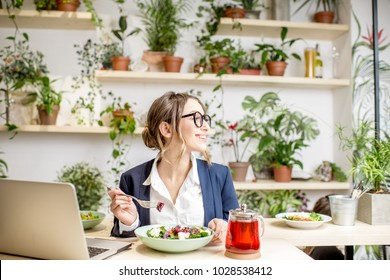 Businesswoman working during the lunch with salad sitting at the vegan restaurant on the beautiful green wall background