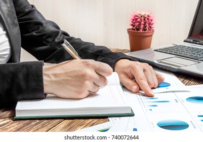 Businesswoman working with financial graphs and writing information to notepad. Business concept.