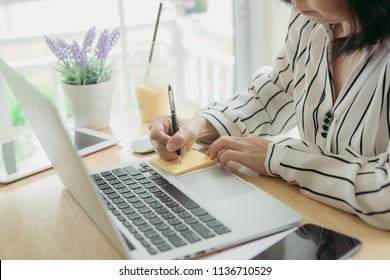 Businesswoman working handwriting notes postit at her table office
