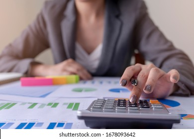 Businesswoman working with holding a pen and using a calculator to calculate the numbers of static. Finance accounting concept