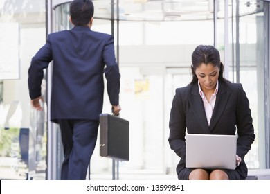 Businesswoman working at laptop outside office