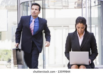 Businesswoman working at laptop outside office building